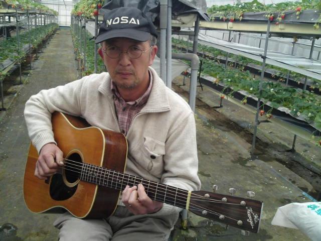 扶桑町産の人が扶桑町産のギターを弾く図